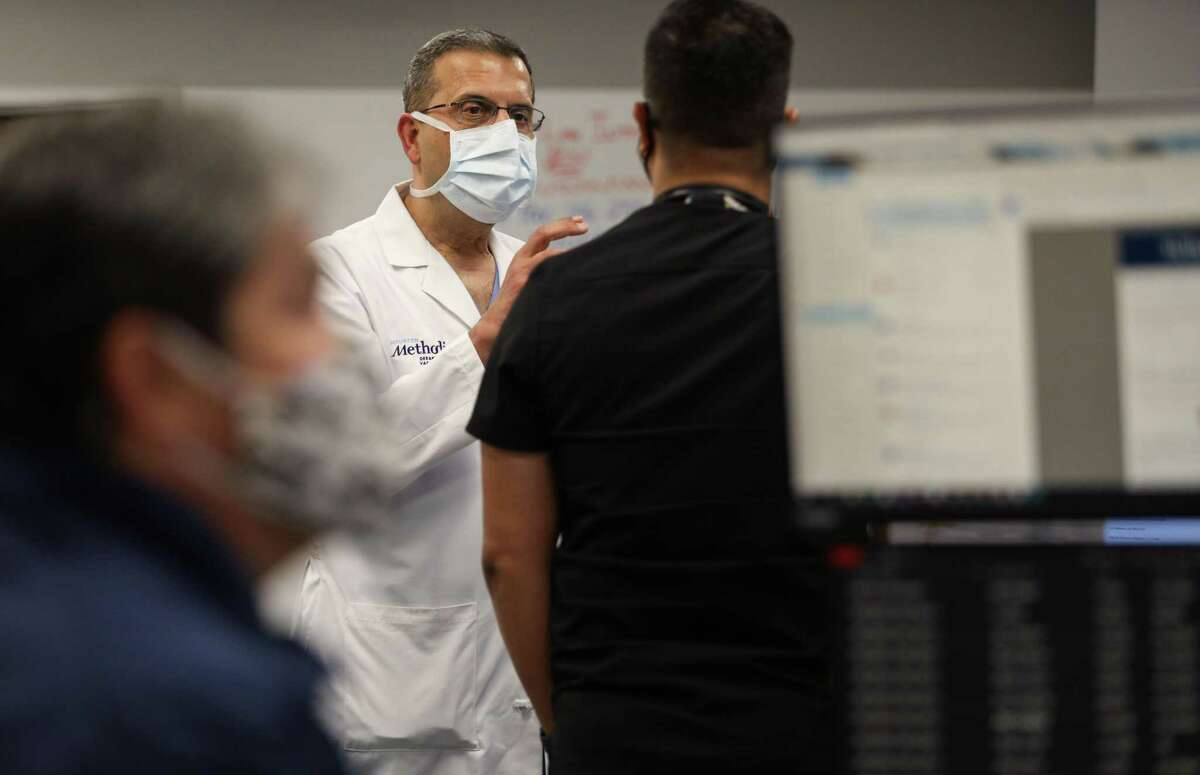Dr. Faisal Masud, center, medical director of the center for critical care, talks with Jay Paul Bedruz, a nurse manager, in the virtual intensive care unit Wednesday, June 23, 2021, at Houston Methodist Hospital in Houston.