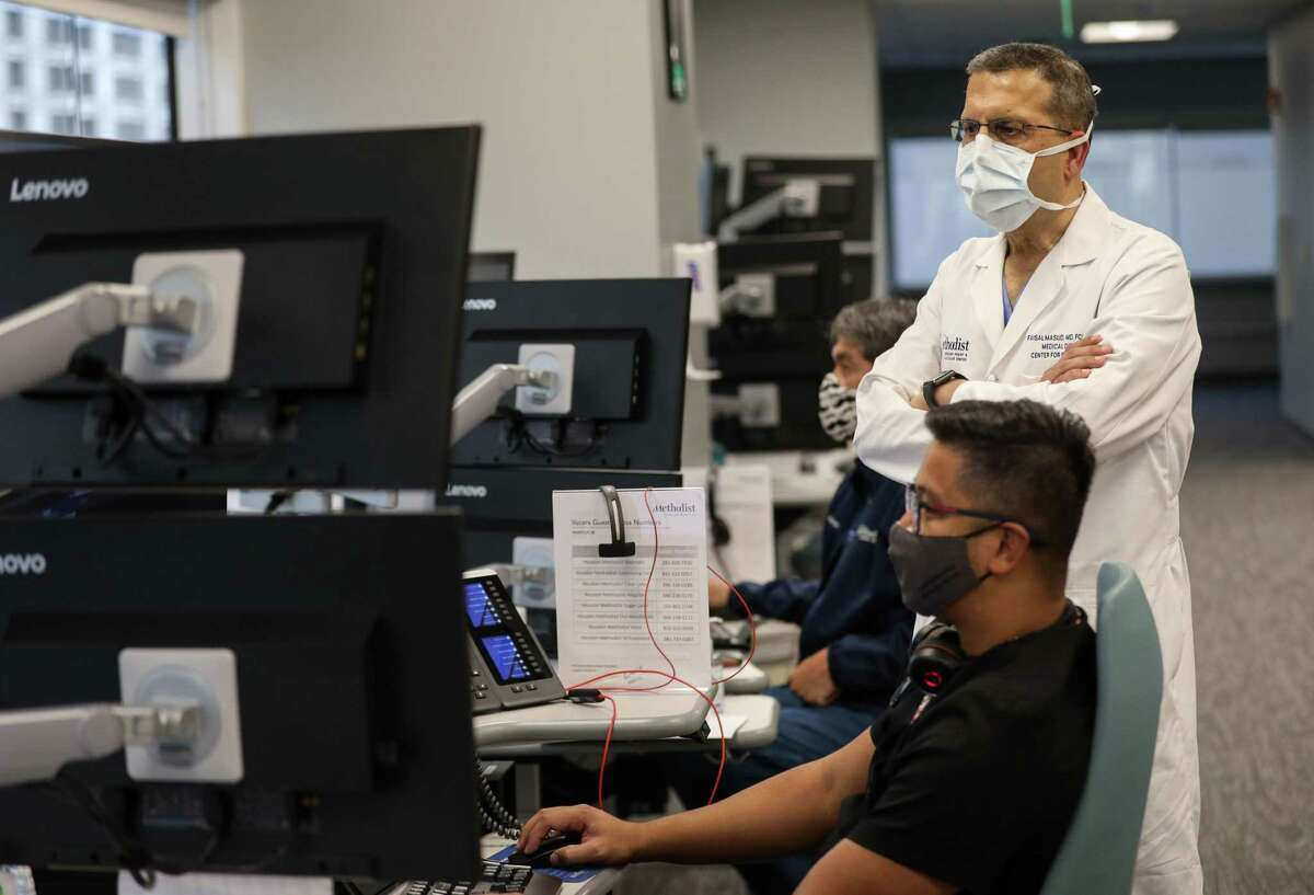 Dr. Faisal Masud, right, medical director of the center for critical care, and Jay Paul Bedruz, a nurse manager, check on patients in the virtual intensive care unit Wednesday, June 23, 2021, at Houston Methodist Hospital in Houston.