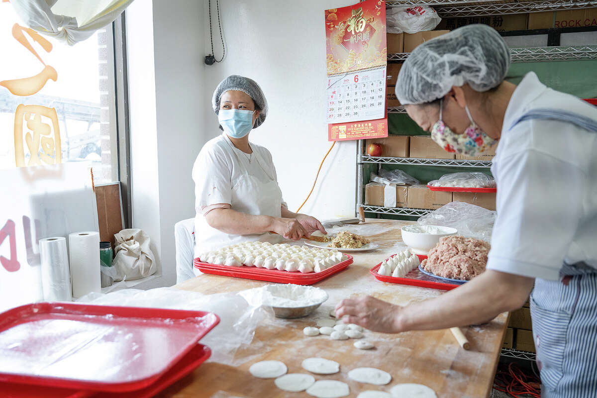 These master dumpling makers fold and fill right in the frozen dumpling display cabinet from Kingdom of Dumpling.