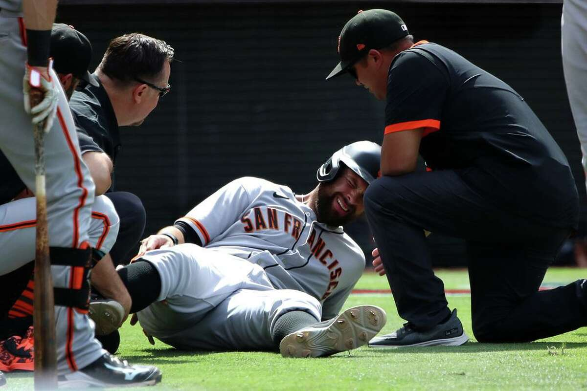 ANAHEIM, CALIFORNIA - JUNE 23: Brandon Belt #9 of the San Francisco Giants lies on the ground in pain after running home in the eighth inning against the Los Angeles Angels at Angel Stadium of Anaheim on June 23, 2021 in Anaheim, California. (Photo by Katelyn Mulcahy/Getty Images)