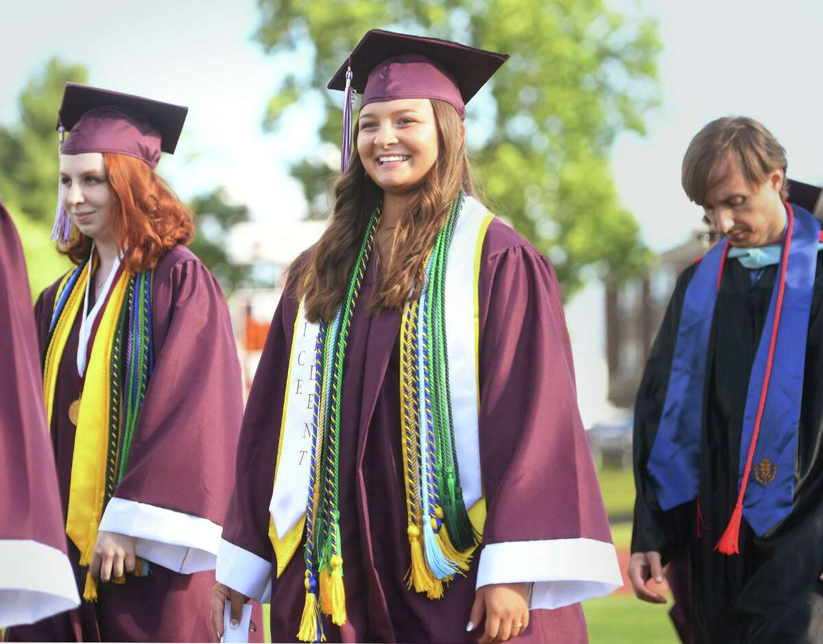 Valedictorian Audrey Keener, left, and class Vice President Ashlynn Ehrhard march near the front of the procession into the Bethel High School graduation ceremony at the school in Bethel, Conn. on Wednesday, June 23, 2021.