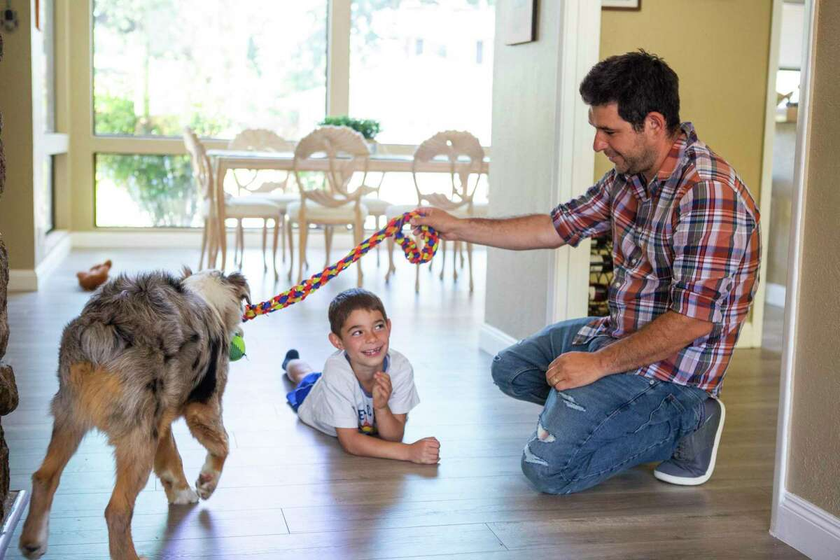Alan Kornfeld (center) and his father, Shay Kornfeld, play with the family dog, Bullet, on the floor of the family house in Walnut Creek. Shay and his wife cashed out some of their Dogecoin earnings to buy a $1,500 dog at one point, and they like to joke that Bullet is now a $18,000 puppy.