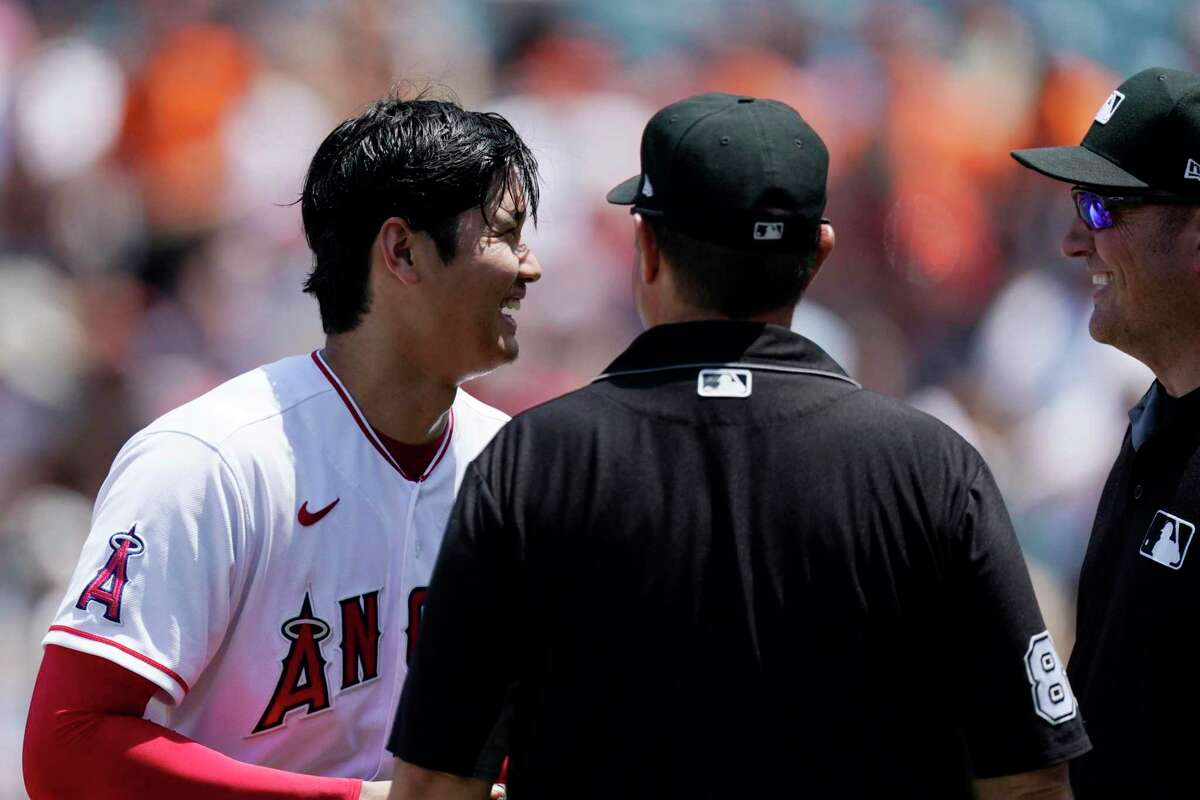Los Angeles Angels starting pitcher Shohei Ohtani laughs after having his belt, glove and hat checked by umpires following the second inning of a baseball game against the San Francisco Giants Wednesday, June 23, 2021, in Anaheim, Calif. (AP Photo/Mark J. Terrill)