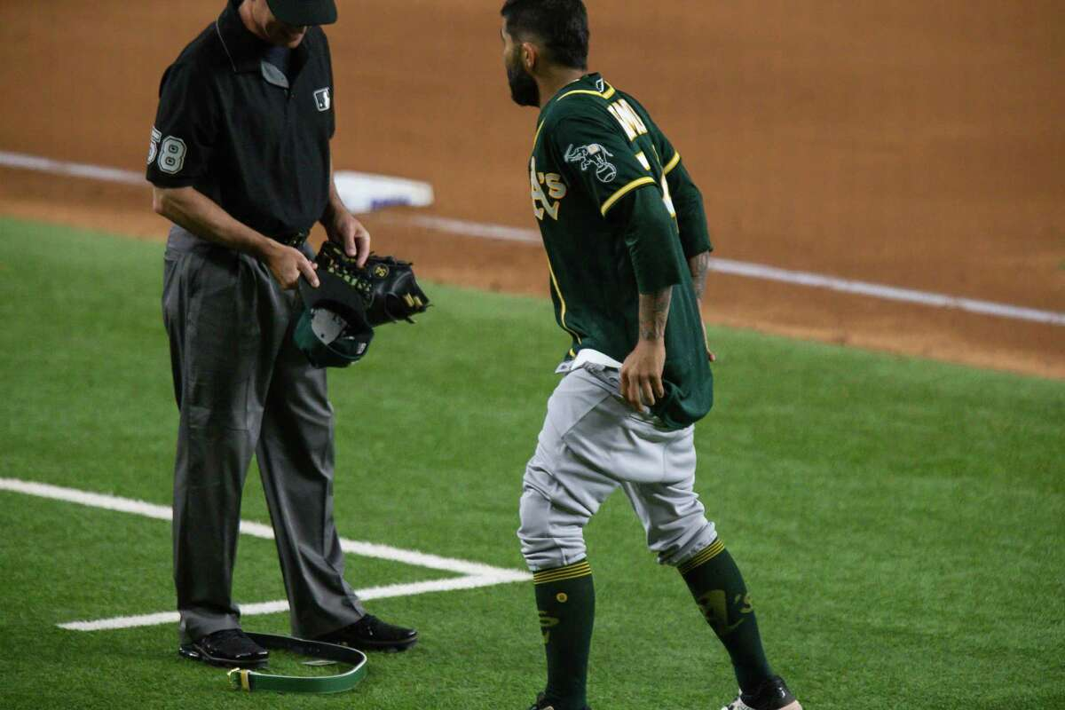 ARLINGTON, TX - JUNE 22: Oakland Athletics Pitcher Sergio Romo (54) gives third base umpire Dan Iassogna his hat, glove, and belt to check and pulls down his pants during the Texas Rangers game versus the Oakland Athletics on Jun 22nd, 2021, at Globe Life Field in Arlington, TX. (Photo by Aric Becker/Icon Sportswire via Getty Images)