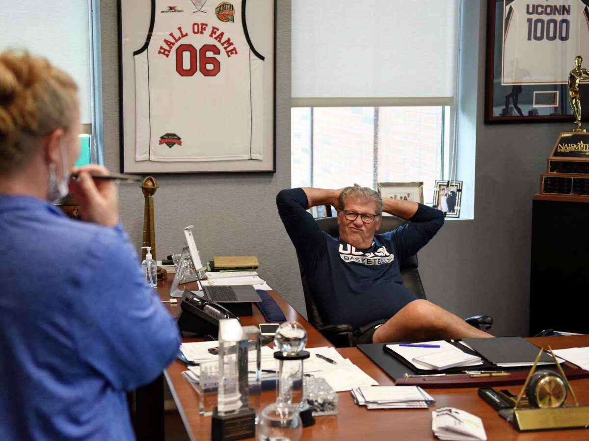 UConn women's basketball coach Geno Auriemma chats with Director of Operations Sarah Darras in his office at the Werth Family UConn Basketball Champions Center on the UConn main campus in Storrs, Conn. Monday, June 14, 2021.