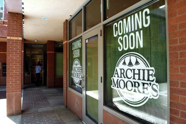 Signs posted on the windows in a courtyard at 988 Main Street in Branford announce the soon to open Archie Moore's Bar & Restaurant on June 23, 2021.