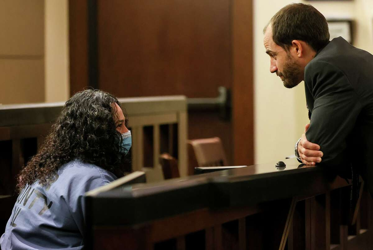Attorney Nathan Fennell, right, talks with defendant Janie Villeda in court Wednesday. The Bexar County Public Defender's Office is challenging the constitutionality of Gov. Greg Abbott's executive order prohibiting early release for good behavior.
