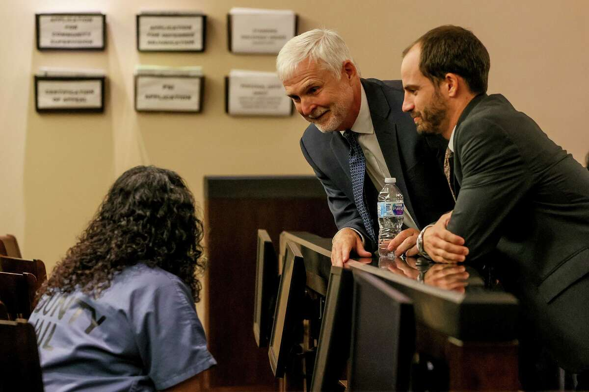 Bexar County Public Defender Michael Young, center, and attorney Nathan Fennell talk with defendant Janie Villeda in court Wednesday. The Bexar County Public Defender's Office is challenging the constitutionality of Gov. Greg Abbott's executive order prohibiting early release for good behavior.