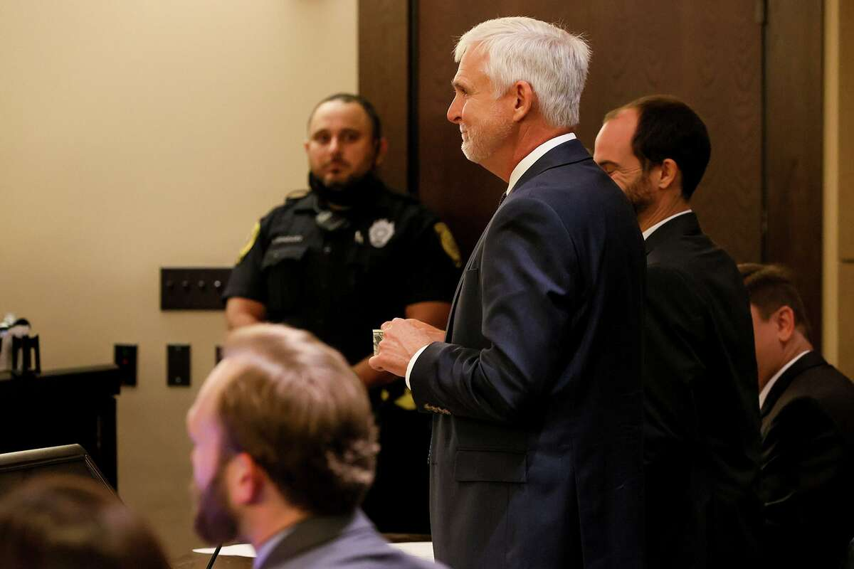 Bexar County Public Defender Michael Young, center, holds a $1 bill after state District Judge Ron Rangel agreed to release defendant Janie Villeda on bail for that amount Wednesday.