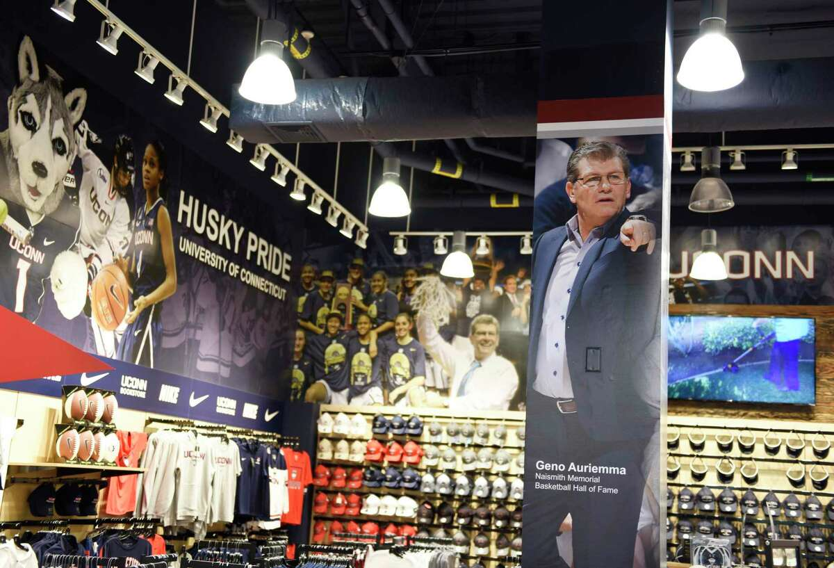 A photo of men's basketball coach Geno Auriemma is displayed among Huskies basketball apparel in the UConn Bookstore on the UConn main campus in Storrs, Conn., photographed on Wednesday, June 9, 2021.