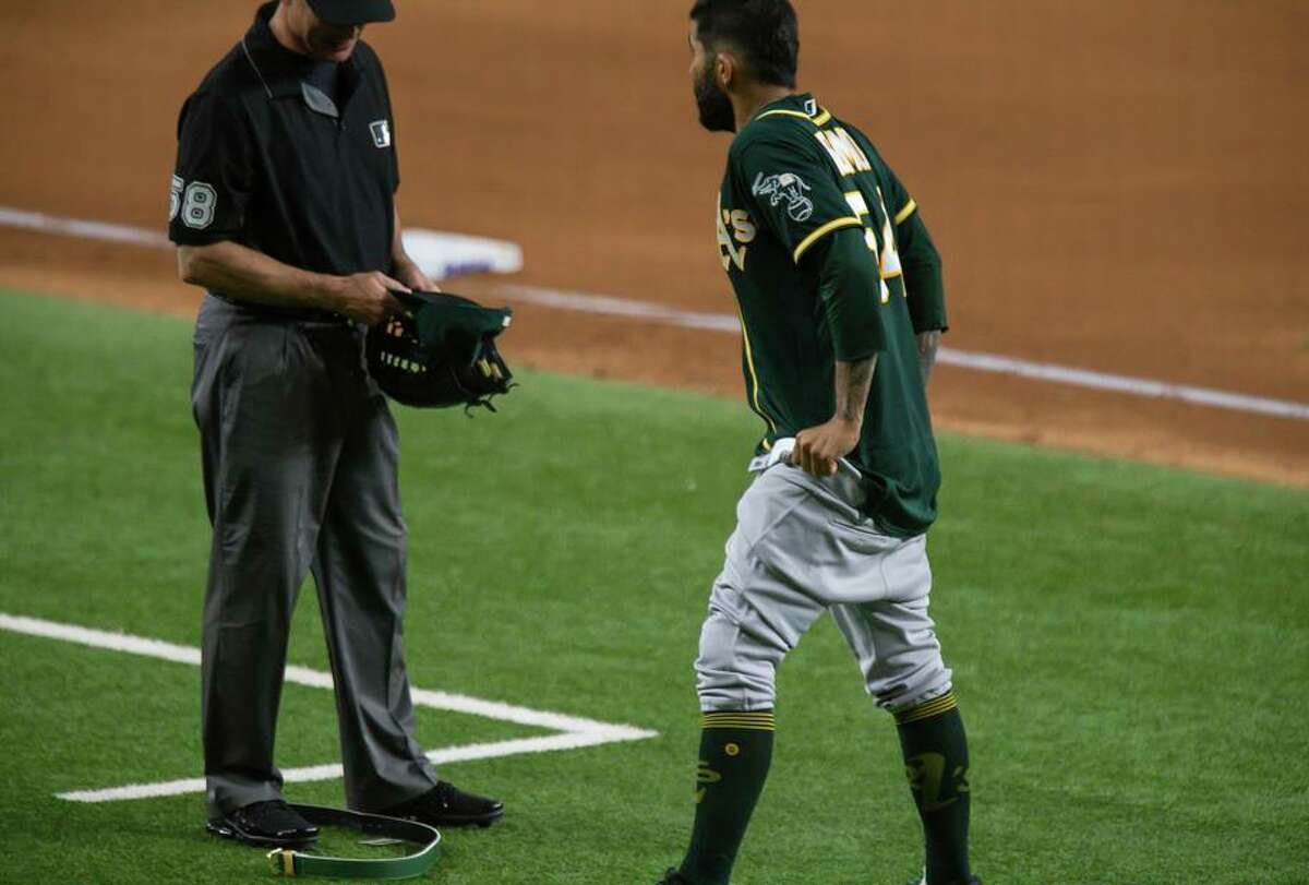 The A's Sergio Romo drops his pants after umpire Dan Iassogna checked his hat, glove and belt for foreign substances.