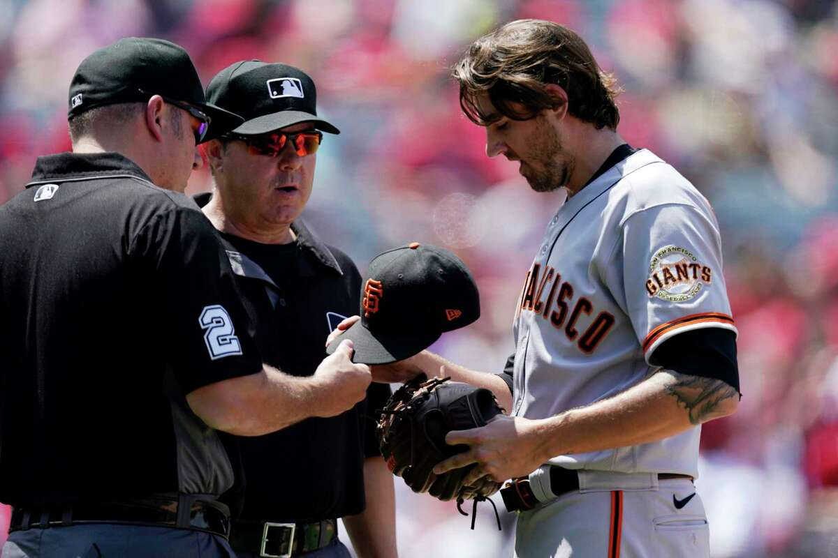 San Francisco Giants starting pitcher Kevin Gausman, right, has his hat, glove and belt checked by umpires after the fourth inning of a baseball game against the Los Angeles Angels Wednesday, June 23, 2021, in Anaheim, Calif. (AP Photo/Mark J. Terrill)