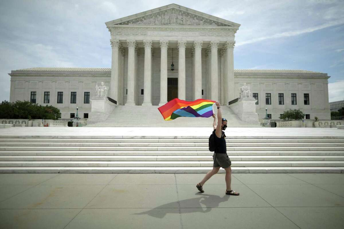 Joseph Fons holds a Pride flag as he walks back and forth in front of the U.S. Supreme Court building last June after the court ruled that LGBTQ people can not be disciplined or fired based on their sexual orientation.
