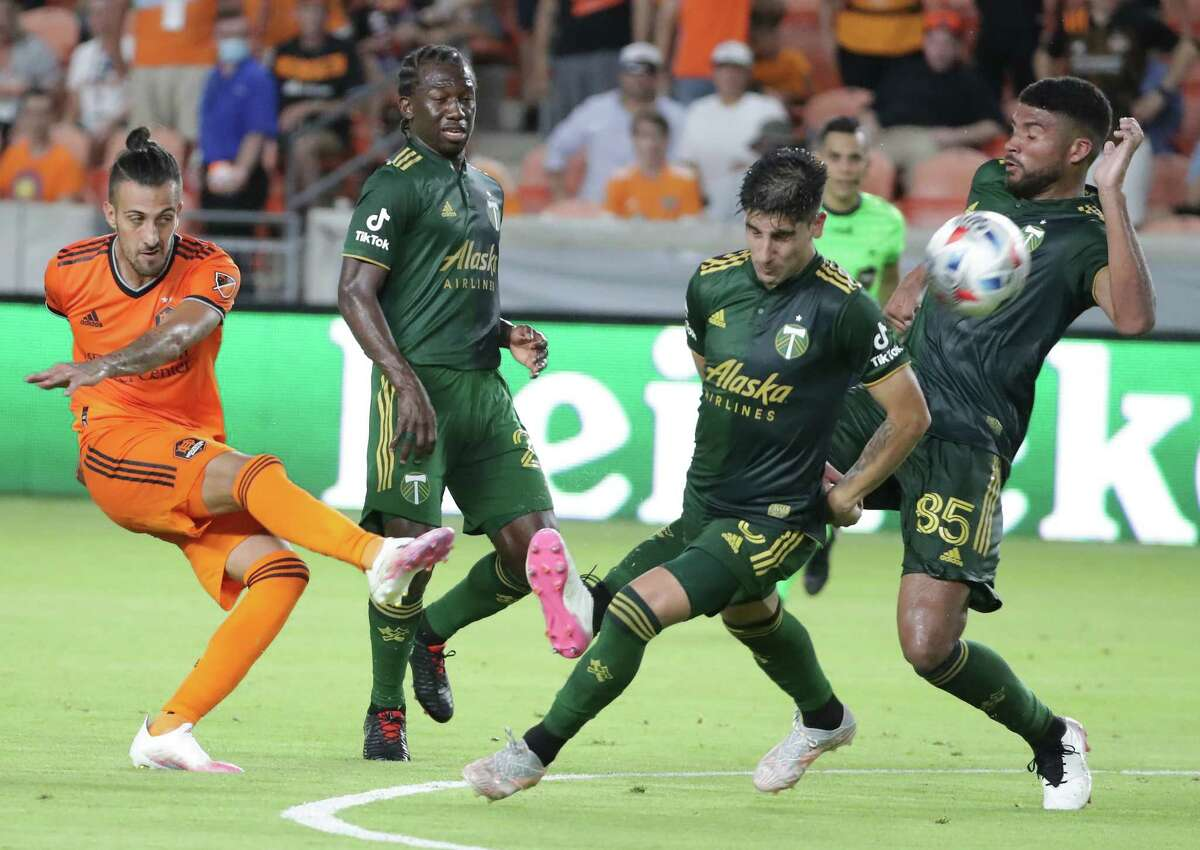 Houston Dynamo forward Maximiliano Urruti shoots the ball past Portland Timbers defenders during second half action at BBVA Compass Stadium on Wednesday, June 23, 2021, in Houston.