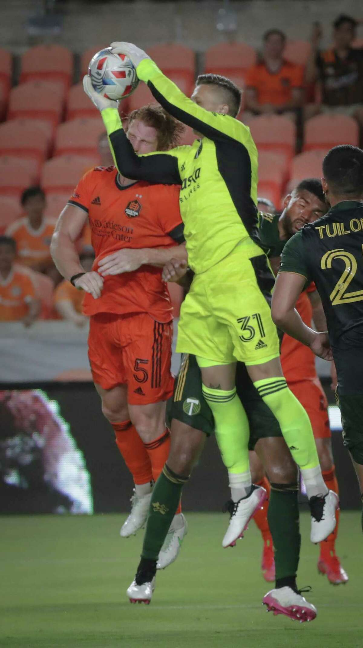 Portland Timbers goalkeeper Aljaz Ivacic grabs the ball before Houston Dynamo defender Tim Parker's header shot attempt during second half action at BBVA Compass Stadium on Wednesday, June 23, 2021, in Houston.