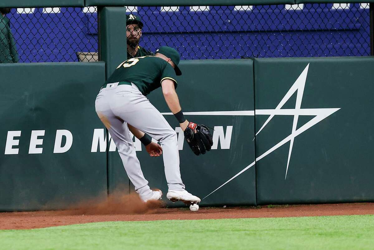 Athletics left fielder Seth Brown scrambles to corral a hit by the Rangers' Eli White in the A's loss in Arlington, Texas. The A's lost after leading 3-2 in the seventh inning.