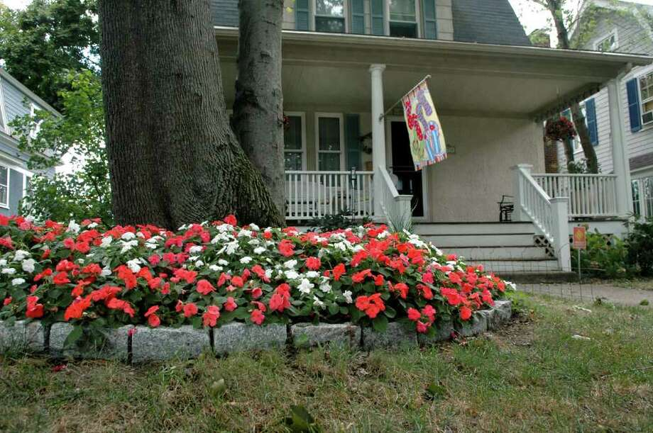 The Fairfield Historic District Commission has some pretty tough rules, including one that does not allow the use of Belgium blocks. George Coles used the blocks to make a circular flower bed and planted pink and white impatiens around the tree in his front yard on the Old Post Road.  Colesworthy and his wife, Maryann, got the notice of violation, dated Aug. 20. Photo: Cathy Zuraw / Connecticut Post
