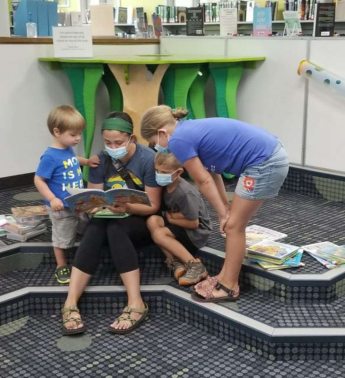 Library patron Maggie Popp reads to Jude, Hayden and Naomi while their siblings look for books.