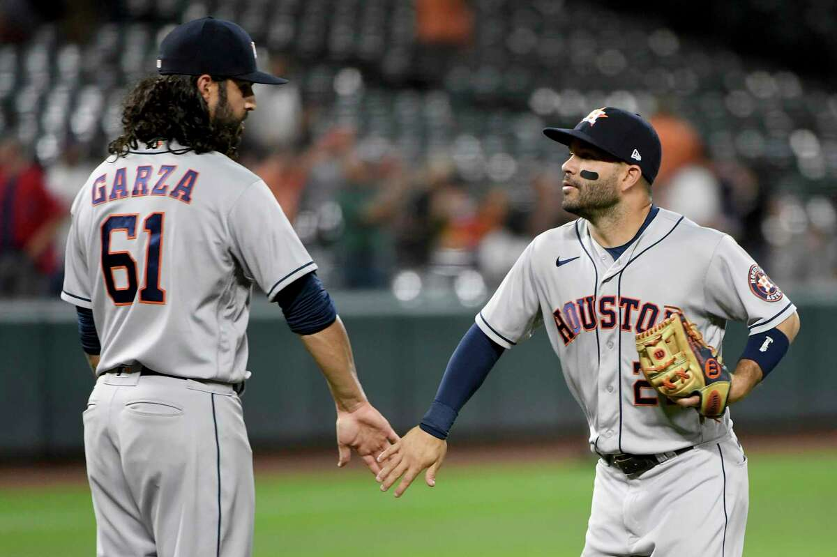 Houston Astros' Ralph Garza Jr. (61) and Jose Altuve celebrate after defeating the Baltimore Orioles in a baseball game, Wednesday, June 23, 2021, in Baltimore. (AP Photo/Will Newton)