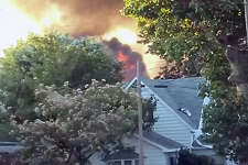 Flames leap above trees in a Meredosia neighborhood after an explosion and ensuing fire.