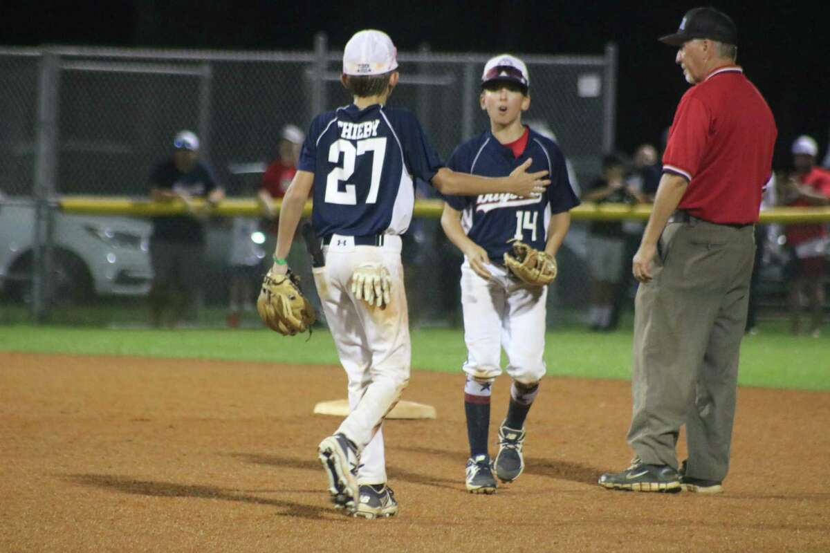 Bayside's Torin Thiery congratulates second baseman Marc Amsler, following his nice sixth-inning gem, one of several that kept NASA Area Little League off the scoreboard for the final five frames.
