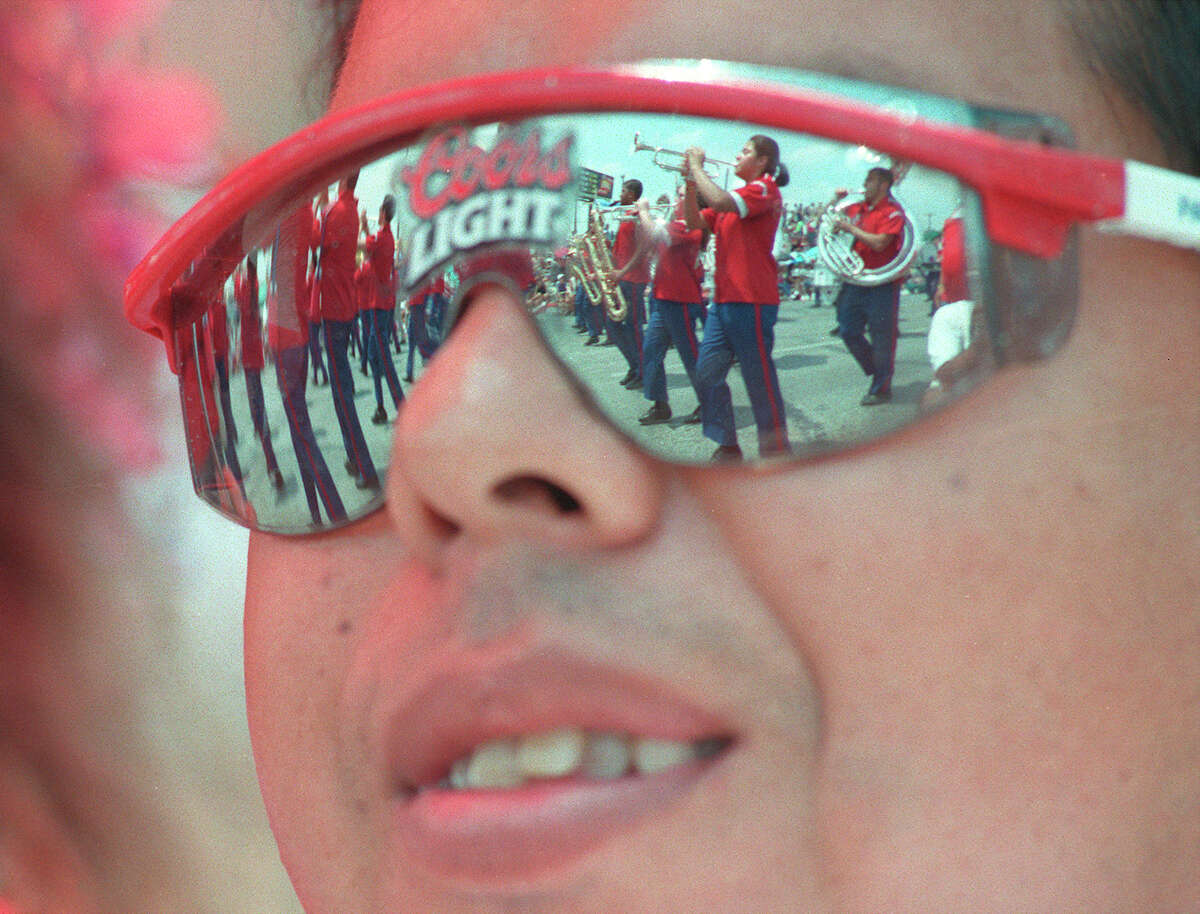 Participants in the 1999 Battle of Flowers Parade are reflected in the sunglasses of Frank Martinez.