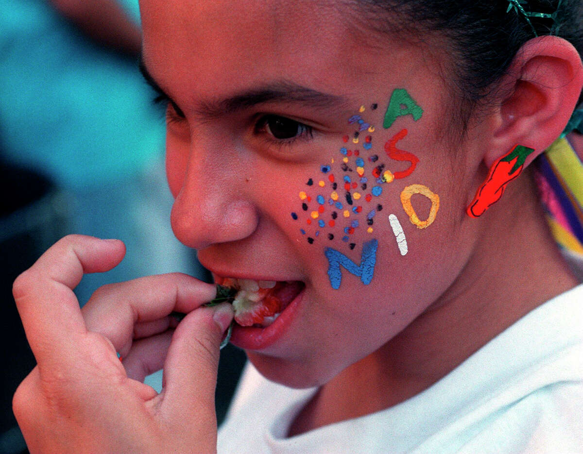 Ten-year-old Nicole Garcia eats a strawberry with her face painted and dressed in her fiesta outfit during Night in Old San Antonio (NIOSA), 2001.