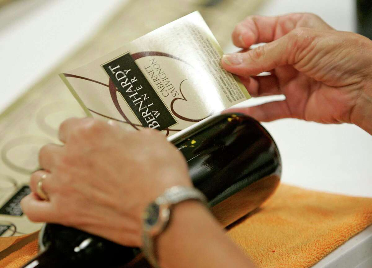 A worker affixes the winery's label to a bottle of wine at Bernhardt Winery in Plantersville. Bernhardt Winery has partnered with Margaritaville on a package for its Summer Sunday Concert Series.
