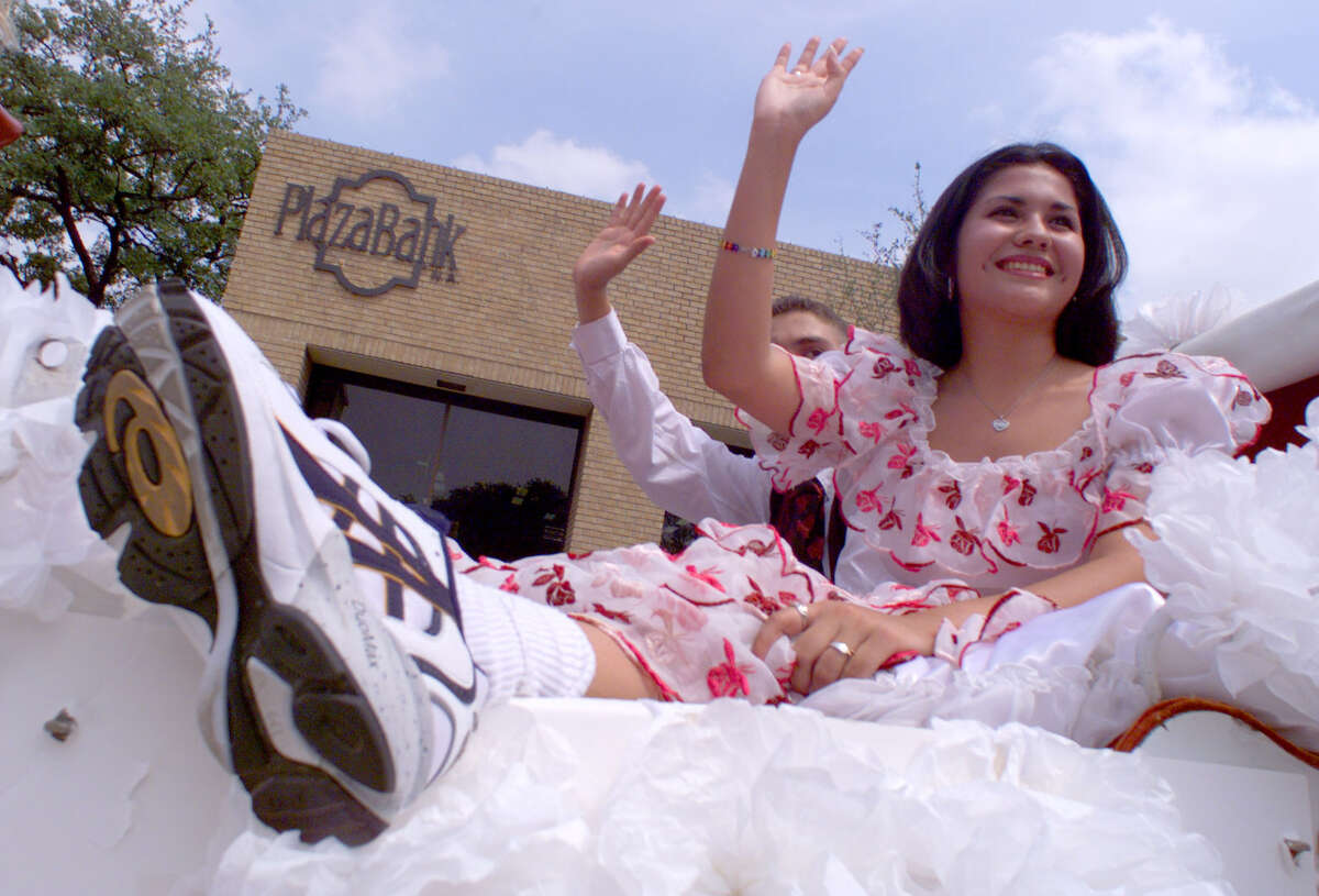 Nina Duran, Queen of the International Black and White Ball, shows her shoes for spectators at the Battle of the Flowers parade in 1999.