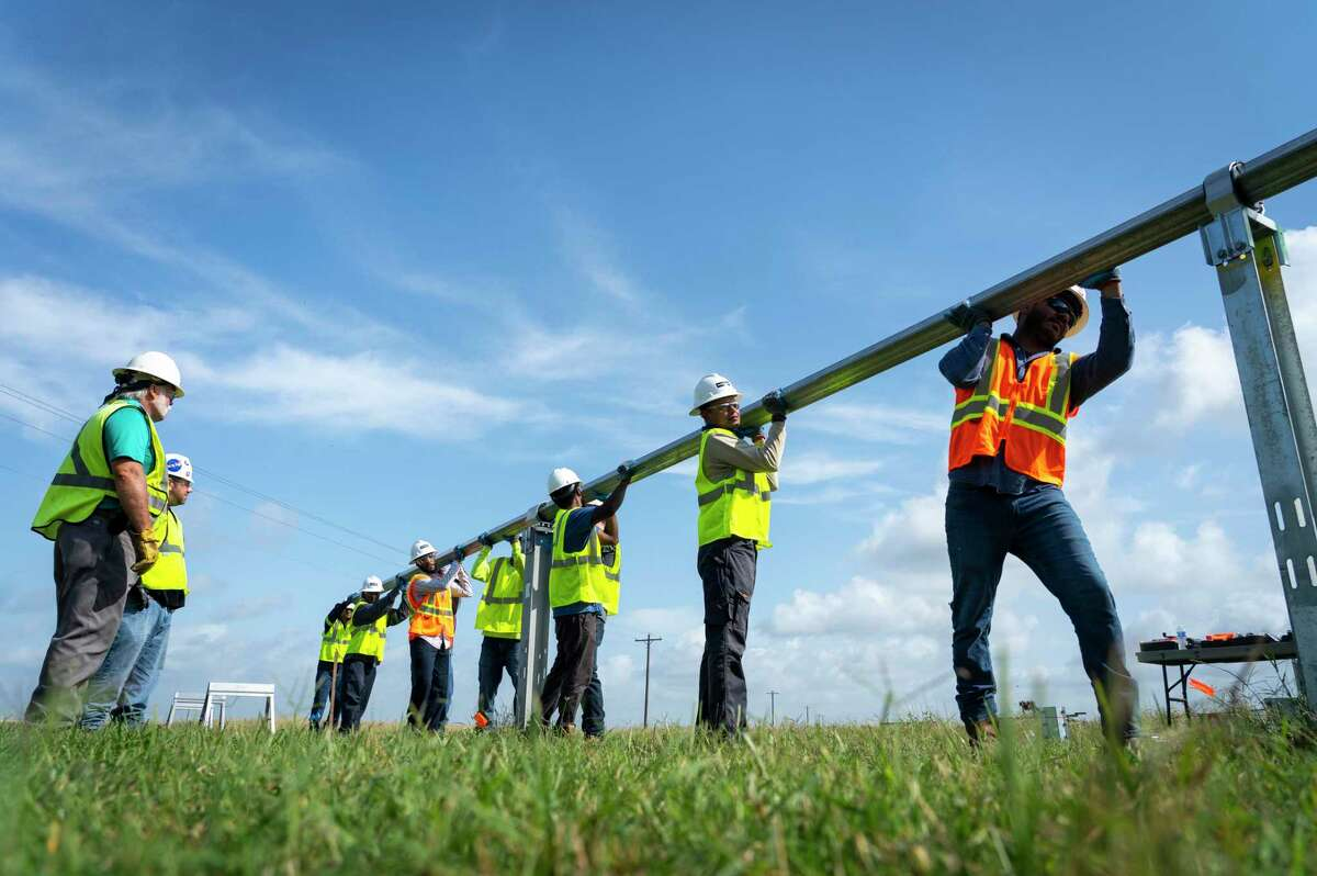 Students move a beam into place that will support solar panels during a training session, Tuesday, May 11, 2021, at a large solar farm south of El Campo. Lone Star College has partnered with Workrise to provide free training for workers who want to work in the solar industry.