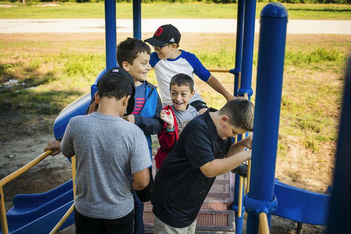 From left, Jaxson Lewis, 10, Johnny Keys, 10, Grant Beck, 9, Noah Keys, 7, and Michael DeHaven, 10, all former members of a now disbanded Cub Scout pack comprised of Blessed Sacrament students, play on the playground at the Village of Sanford Park Wednesday, June 23, 2021. The boys and their scout moms met with Village of Sanford President Dolores Porte to deliver a donation of the troop's last remaining funds to assist in the effort to revitalize the damaged playground. (Katy Kildee/kkildee@mdn.net)