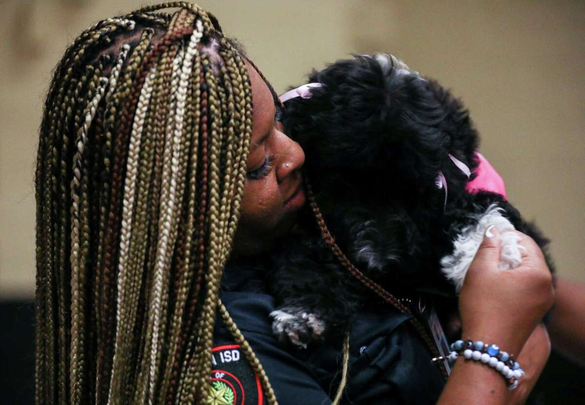 Torre Mathieu, a Houston ISD Police detective, holds Jamaica, a 14-week-old comfort dog, Thursday, June 24, 2021, at Fondren Middle School in Houston.