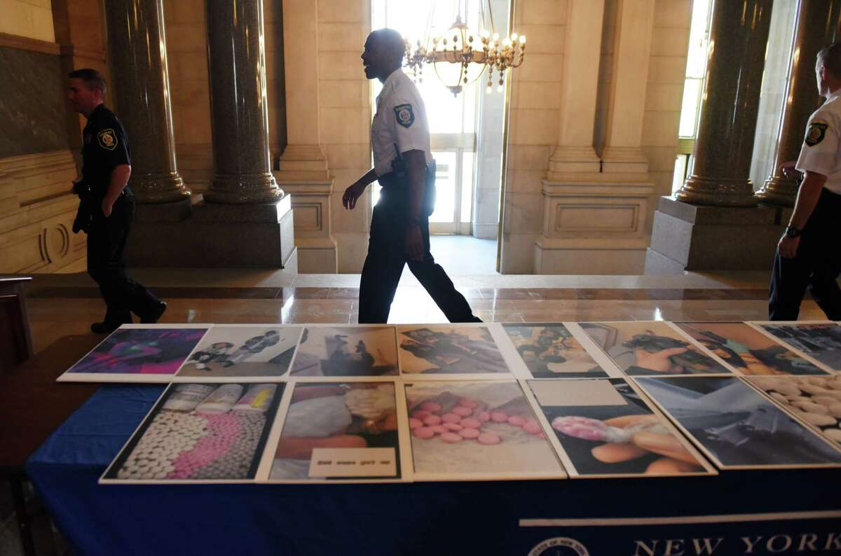 """Albany Police Chief Eric Hawkins walks past a collection of photos used as evidence in a narcotics and weapons trafficking investigation in the city on Thursday, June 24, 2021, during a press conference outside New York State Attorney General Letitia James' offices at the Capitol in Albany, N.Y. The investigation was a joint effort by local police and state authorities, who targeted so-called """"uptown"""" and """"downtown"""" gangs suspected of criminal activity in Albany. (Will Waldron/Times Union)"""