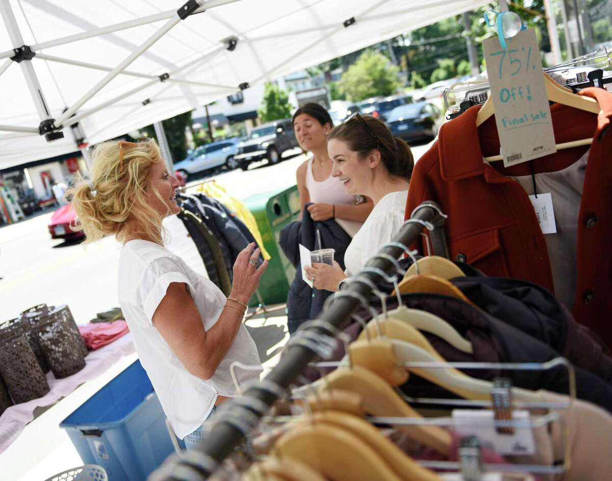 Originals owner Sigrid Van Tuijl, left, chats with shoppers during the Old Greenwich Merchants Association Sidewalk Sale in downtown Old Greenwich, Conn. Thursday, June 24, 2021. More than 20 stores participated in the event, offering extreme discounts on merchandise displayed outside along the sidewalk. Many shops remained open until 8 p.m., when the sale was followed by live entertainment, giveaways, and refreshments. The sidewalk sales will continue through Sunday.