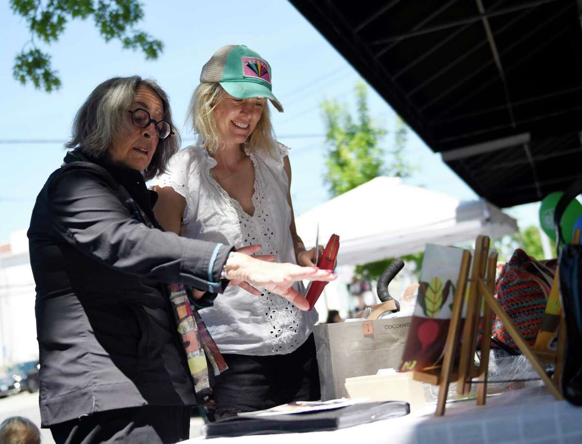 Artist Elena Abrahams, left, shows her work to Riverside resident Millie Stocker during the Old Greenwich Merchants Association Sidewalk Sale in downtown Old Greenwich, Conn. Thursday, June 24, 2021. More than 20 stores participated in the event, offering extreme discounts on merchandise displayed outside along the sidewalk. Many shops remained open until 8 p.m., when the sale was followed by live entertainment, giveaways, and refreshments. The sidewalk sales will continue through Sunday.