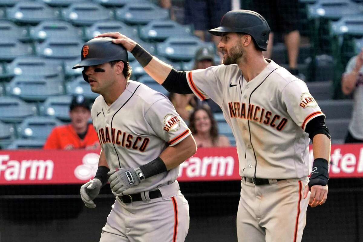 San Francisco Giants' Mike Tauchman, left, gets a pat on the head from Steven Duggar after hitting a three-run home run during the 13th inning of a baseball game against the Los Angeles Angels Wednesday, June 23, 2021, in Anaheim, Calif. (AP Photo/Mark J. Terrill)