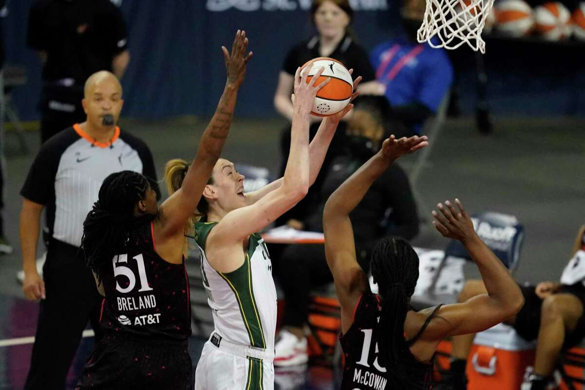 The Seattle Storm's Breanna Stewart, second from left, shoots against the Indiana Fever's Jessica Breland (51) and Teaira McCowan (15) during the first half on June 17.