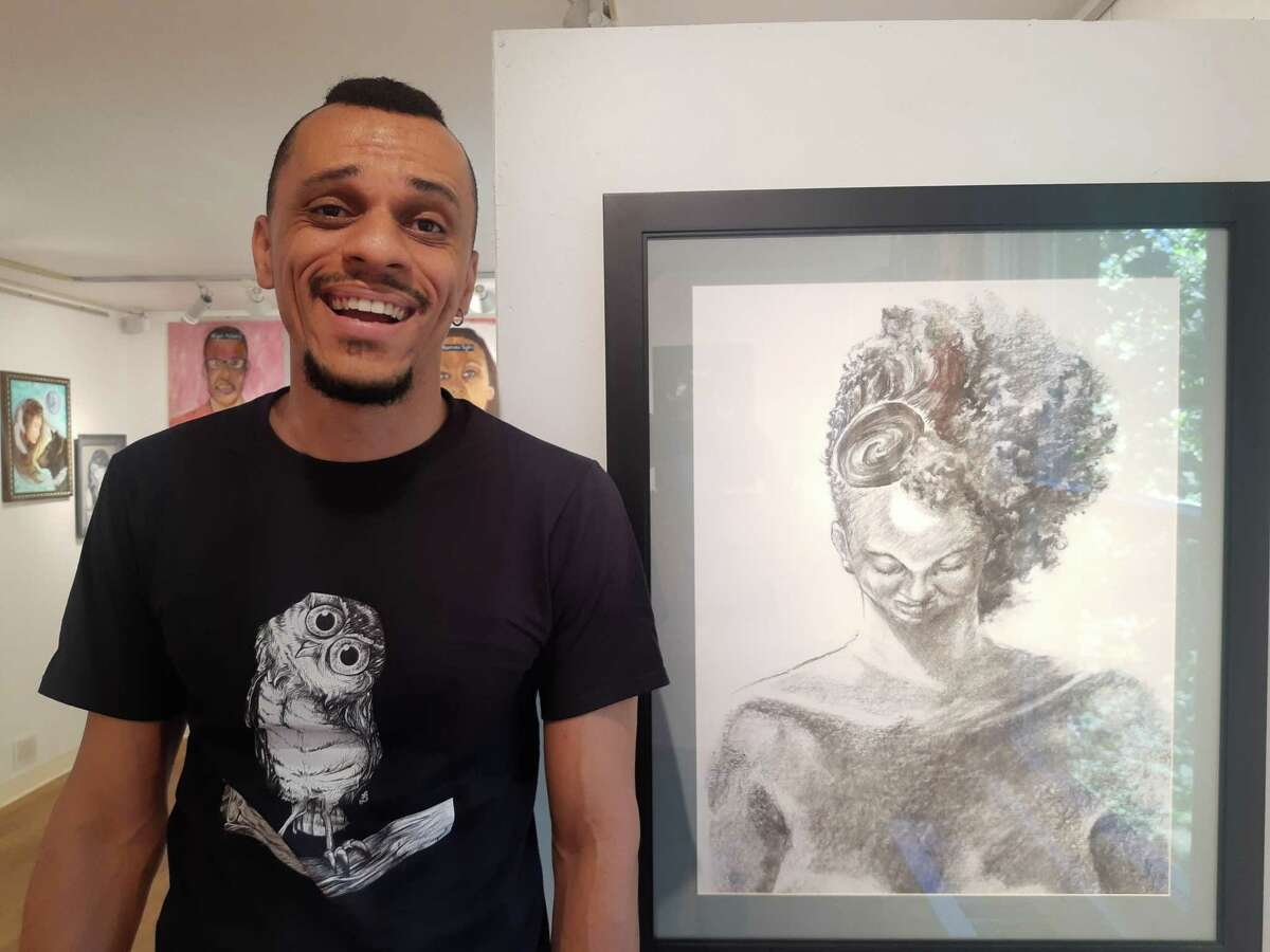 """Artist Franklin Silva with his work, a charcoal on paper piece entitled """"Acceptance."""" Franklin is a Brazilian artist who currently lives in White Plains, N.Y. When he submitted this piece for the show, he wrote: """"The body and mind understanding that who we are is who we are, bringing lightness and allowing us to flourish from the inside out."""""""