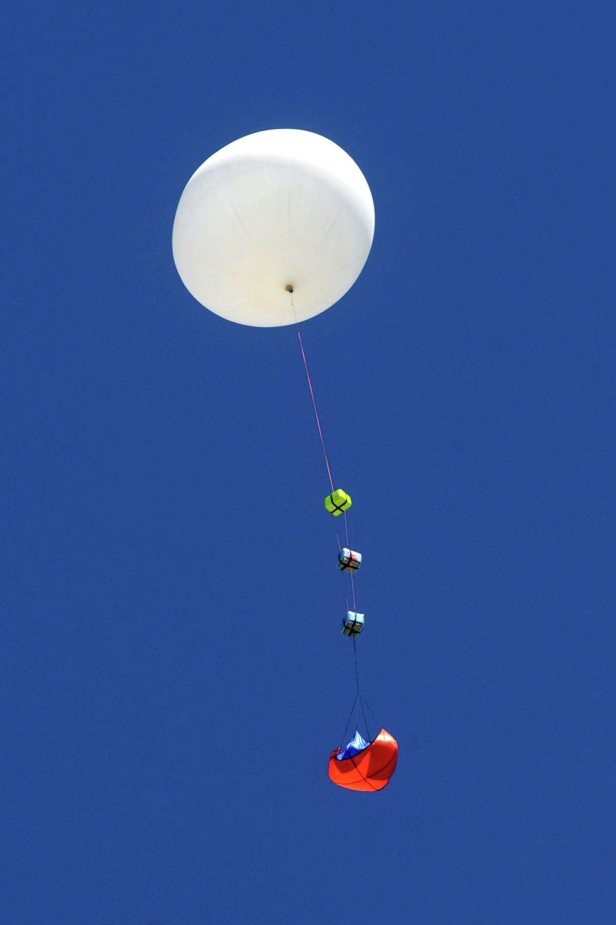 Faculty and students released a helium filled weather balloon from the roof of Fairfield Wheeler Interdistrict Multi-Magnet School, in Bridgeport, Conn. June 24, 2021. Carrying a payload of small experiments, recording devices and cameras, the balloon's release marked the beginning of the school's summer STEM camp.