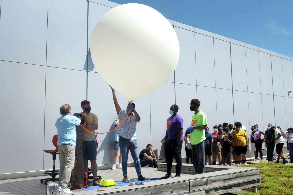 Faculty and students prepare to release a helium filled weather balloon from the roof of Fairfield Wheeler Interdistrict Multi-Magnet School, in Bridgeport, Conn. June 24, 2021. Carrying a payload of small experiments, recording devices and cameras, the balloon's release marked the beginning of the school's summer STEM camp.
