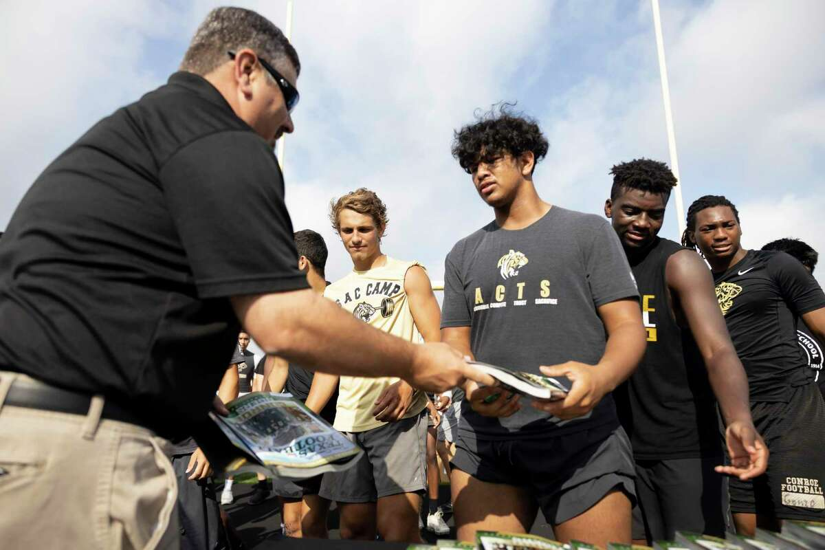 """Conroe High School football players receive a copy of the """"bible"""" of Texas Football at Buddy Moorhead Stadium, Thursday, June 24, 2021, in Conroe. Conroe High School was one of ten high school to be selected to be on the cover."""