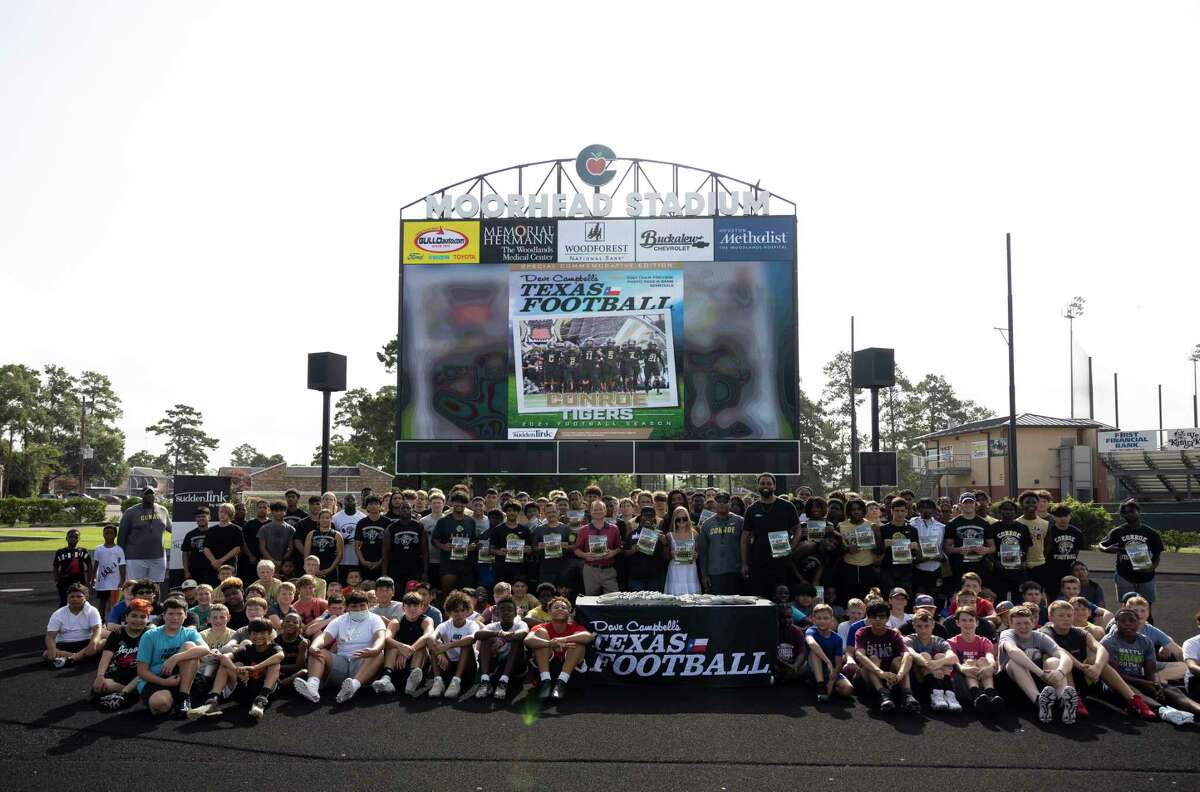 """Administration, students and sponsors pose for a portrait during the presentation of 250 commemorative cover wrapped copies of the """"bible"""" of Texas Football at Buddy Moorhead Stadium, Thursday, June 24, 2021, in Conroe. Conroe High School was one of ten high school to be selected to be on the cover."""