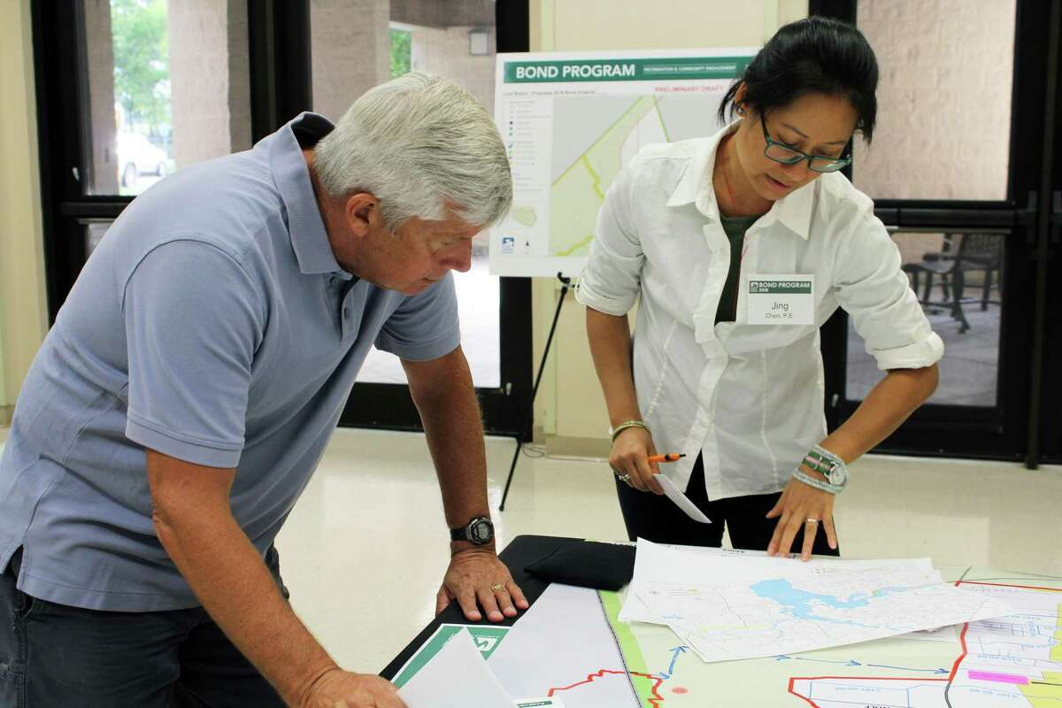Jing Chen, HCFCD floodplain administrator, talks to a Lake Houston resident about the proposed projects for Luce Bayou.
