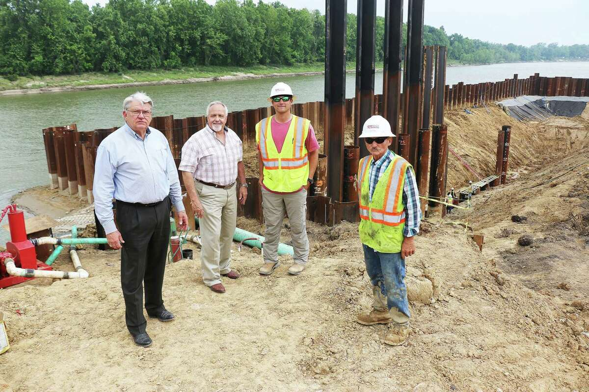 Pct. 2 Commissioner Greg Arthur, Liberty County Judge Jay Knight, Patrick Veale, project engineer, and Paul Duchene stand alongside the huge hole being dug for the pump and intake station at Capers Ridge.