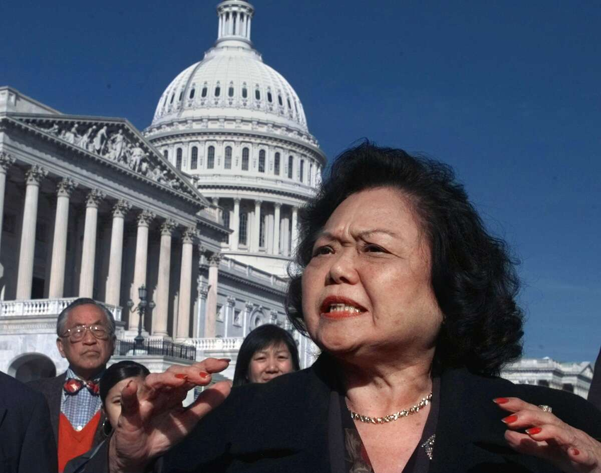 Rep. Patsy Mink, seen here with reporters on Capitol Hill in 1997, was one of Title IX's co-authors. She was also the first woman of color in the House.