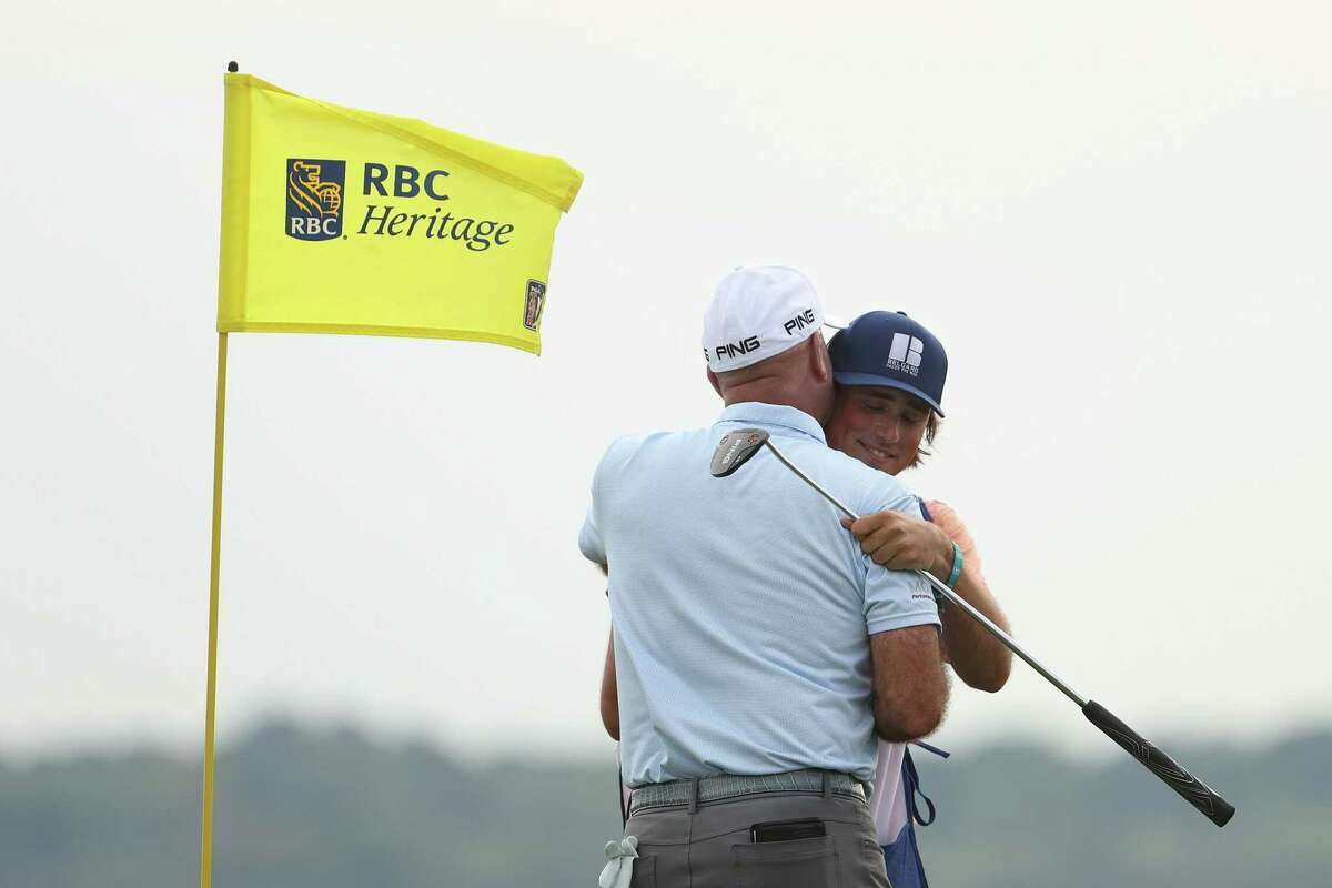Stewart Cink celebrates with his caddie and son, Reagan Cink, on the 18th green after winning the RBC Heritage in April.
