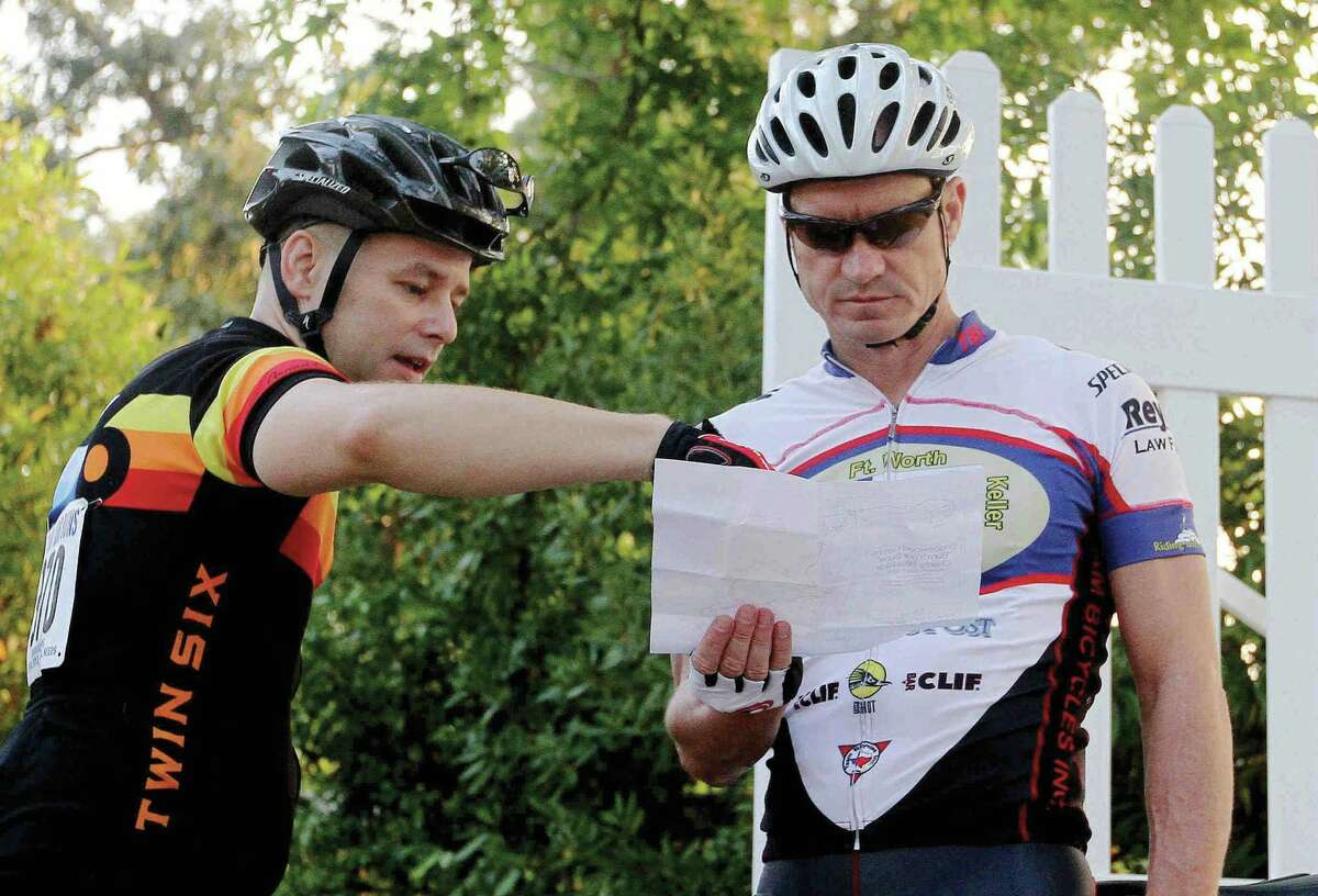 Gregg Goodwin, right, gets some help understanding the route from Don Wodarski before a previous Burn Your Buns Bike Race in Conroe.
