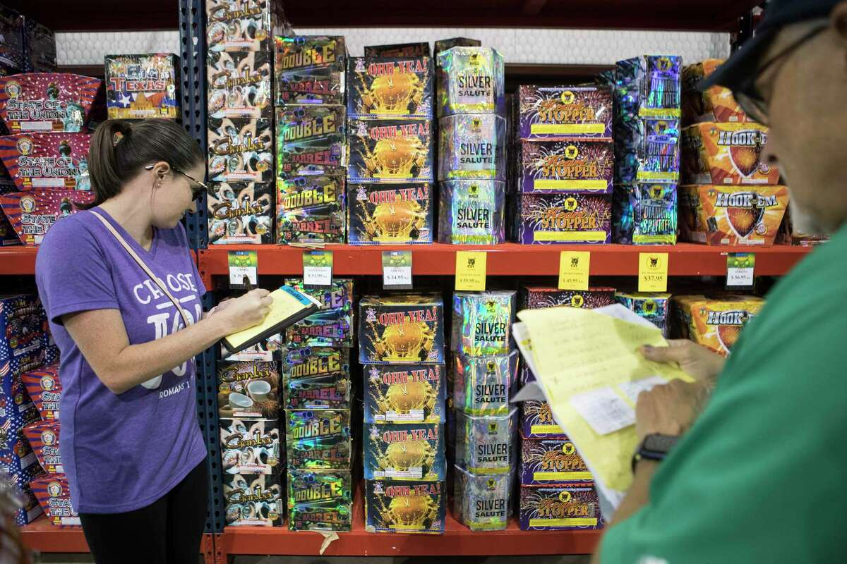Bailee Moore, left, shops for fireworks with her dad, Pat, at American Fireworks Thursday, June 24, 2021 in Pinehurst. Fireworks season started Thursday and supplies won't last, retailers say. They're starting out with only a fraction - less than 10 percent, in some cases - of their usual stock volume as supply chains from China remain strained.