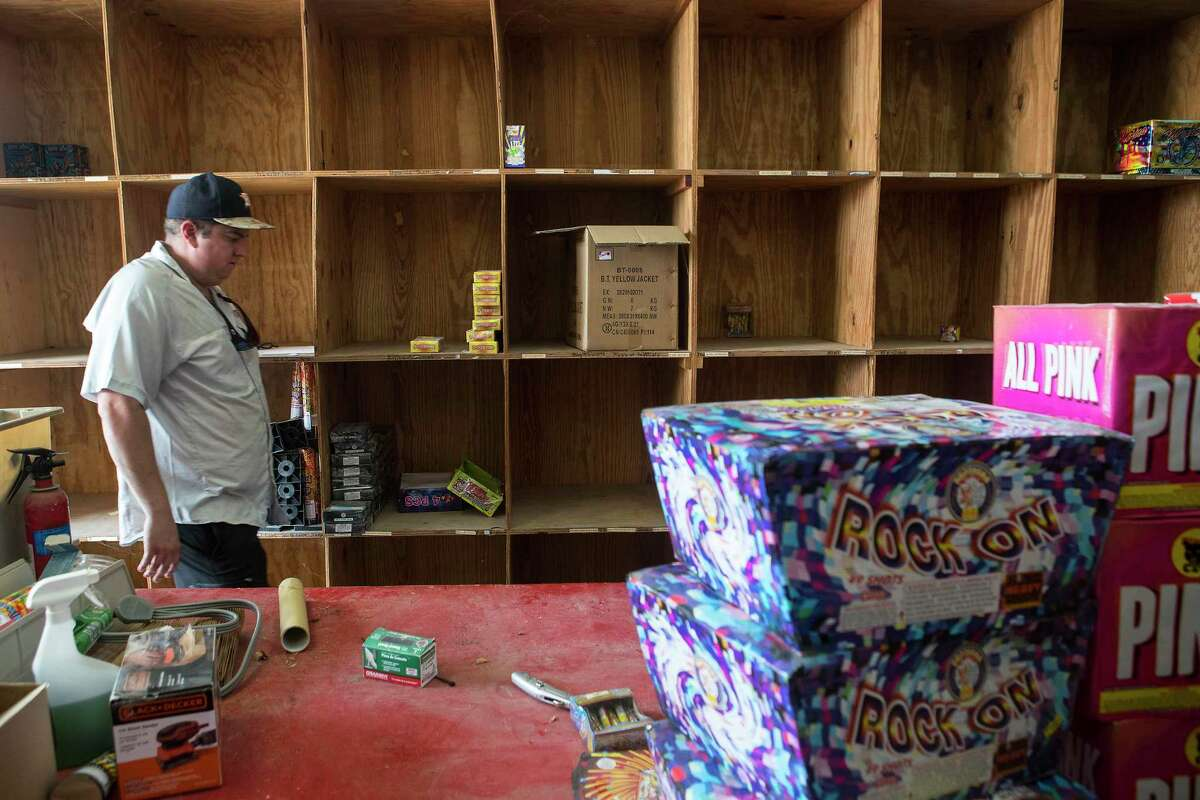 Jaston Davis walks past empty shelves in the warehouse at American Fireworks Thursday, June 24, 2021 in Pinehurst. Fireworks season started Thursday and supplies won't last, retailers say. They're starting out with only a fraction - less than 10 percent, in some cases - of their usual stock volume as supply chains from China remain strained.