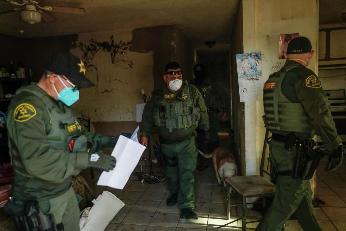Fresno County Sheriff's officers clear a house as they serve an eviction order in Fresno, California. A push to extend California's eviction freeze for struggling tenants is down to the wire, with just days to go before the current moratorium is set to expire on June 30.